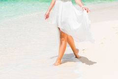 Beautiful young bride in a white wedding dress walking on a trop. Ical sandy beach. feet close-up Stock Image