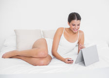 Beautiful young brown haired model in white pajamas using a tablet pc stock photography