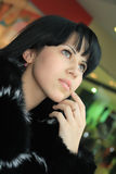 Beautiful young brunette. Portrait of a beautiful young brunette in a fur coat Royalty Free Stock Photography