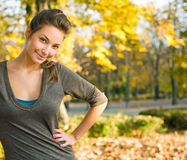 Beautiful young brunette in autumn park. Royalty Free Stock Image