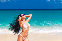 Beautiful young brunette in bikini on a tropical beach Royalty Free Stock Photos