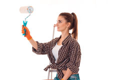 Beautiful young brunette builder girl in uniform makes renovation with paint roller in her hands isolated on white Stock Photos