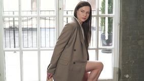 Beautiful young brunette in a business suit. Posing at a photo shoot stock footage