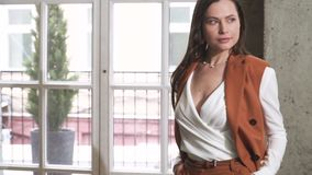 Beautiful young brunette in a business suit. Posing at a photo shoot stock video footage