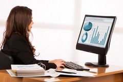 Beautiful young brunette business woman work in her office.  Stock Photo