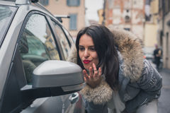 Beautiful young brunette checking lipstick in a rearview mirror Stock Photography