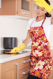 Beautiful young brunette cleaning the kitchen. Royalty Free Stock Photo