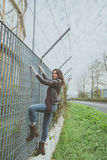 Beautiful young brunette climbing over a fence Stock Image