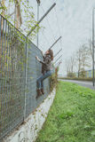 Beautiful young brunette climbing over a fence Stock Photos