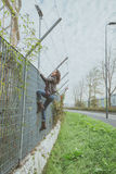 Beautiful young brunette climbing over a fence Royalty Free Stock Images