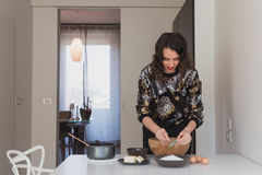 Beautiful young brunette cooking in the kitchen Stock Photography