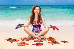 Beautiful young brunette enjoying the sun on the tropical coast. Of red sea stars Stock Photo