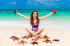 Beautiful young brunette enjoying the sun on the tropical coast. Of red sea stars Royalty Free Stock Photography