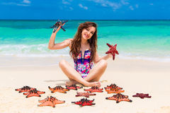 Beautiful young brunette enjoying the sun on the tropical coast. Of red sea stars Stock Image