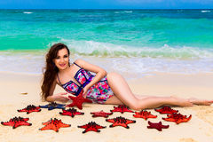Beautiful young brunette enjoying the sun on the tropical coast. Of red sea stars Stock Images