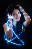 Beautiful young brunette with fairy lights Stock Photos