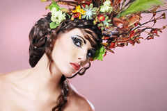 Beautiful young brunette with flowers in hair. Royalty Free Stock Images