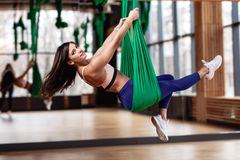 Beautiful young brunette girl is on the aerial silks next to the big mirror in the modern gym stock photography