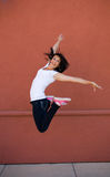 Beautiful young brunette girl doing dancers leap Royalty Free Stock Image