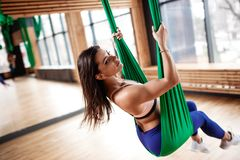 Beautiful young brunette girl  dressed in the sport clothes is doing fitness on the green aerial silk in the gym stock images