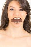 Beautiful young brunette girl eating chocolate Stock Photography