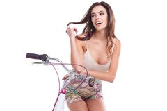 Beautiful girl, sits on a bicycle and winds a curl of hair on her finger. Isolated on white background. Beautiful young brunette girl of European appearance Royalty Free Stock Images