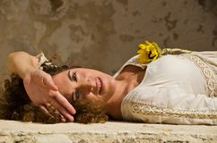Beautiful young brunette girl lie down on wall Royalty Free Stock Photography