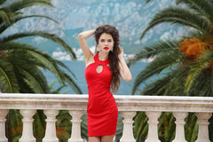 Beautiful young brunette girl model in red dress standing on Bal Stock Photos