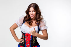 Beautiful young brunette girl of oktoberfest beer stein. Beautiful young brunette girl in dirndl drinks out of oktoberfest beer stein. on white background Royalty Free Stock Photos