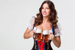 Beautiful young brunette girl of oktoberfest beer stein. Beautiful young brunette girl in dirndl drinks out of oktoberfest beer stein. on white background Stock Images