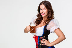 Beautiful young brunette girl of oktoberfest beer stein. Beautiful young brunette girl in dirndl drinks out of oktoberfest beer stein. on white background Royalty Free Stock Photography