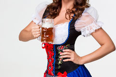 Beautiful young brunette girl of oktoberfest beer stein. Beautiful young brunette girl in dirndl drinks out of oktoberfest beer stein. on white background Royalty Free Stock Images
