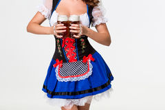 Beautiful young brunette girl of oktoberfest beer stein. Beautiful young brunette girl in dirndl drinks out of oktoberfest beer stein. on white background Stock Photo