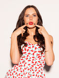 Beautiful young brunette girl posing in a short summer dress and red lips kiss does the finger at his lips. Indoor. Close up. Warm Stock Images