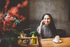 Beautiful young brunette girl talking on mobile phone at wooden table near window and drinking coffee in cafe decorated Royalty Free Stock Photography