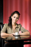 Beautiful young brunette and her coffee. Stock Image
