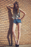 Beautiful young brunette in jeans clothes posing outdoor near red brick wall royalty free stock photo
