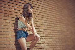Beautiful young brunette in jeans clothes posing outdoor near red brick wall Stock Images