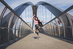 Beautiful young brunette jumping on a bridge Royalty Free Stock Photo