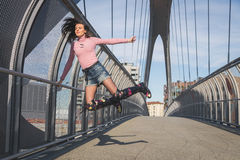 Beautiful young brunette jumping on a bridge Royalty Free Stock Images
