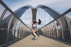 Beautiful young brunette jumping on a bridge Royalty Free Stock Photos
