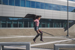 Beautiful young brunette jumping in the city streets Stock Photography
