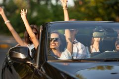 Beautiful young brunette lady in sunglasses sits with friends in a black cabriolet smiles and holding her hands up on a royalty free stock photo