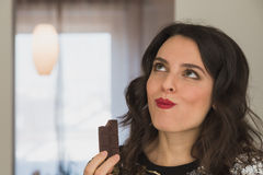 Beautiful young brunette with long hair eating chocolate Stock Photography