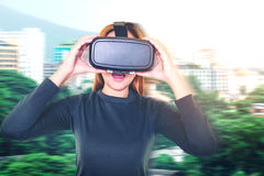 Beautiful young brunette with long hair wearing virtual reality. Headset in city Royalty Free Stock Photography