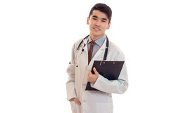 Beautiful young brunette man doctor in white uniform with stethoscope looking at the camera isolated in studio Royalty Free Stock Images