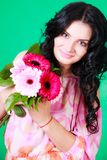 Beautiful young brunette in a pink dress with a bunch of gerbera Stock Images