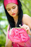 Beautiful young brunette with pink purse Royalty Free Stock Photo