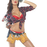 Beautiful young brunette in a plaid shirt. High fashion glamour model in Daisy duke shorts, tool belt, red bra with a screw gun Royalty Free Stock Photos