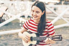 A beautiful young brunette plays an ukulele acoustic guitar royalty free stock photo